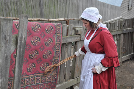 """Beating a rug in the mid 1850s. The object in her hand was known as a """"carpet beater"""" and took a fairly strong girl to rid the rug of the accumulation of dirt from the winter. (Sovereign Hill Education Blog, servant-carpet-beating.)"""