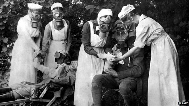 Nurses in gas masks treat soldiers after a gas attack.