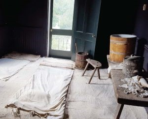 The interior of the Pest House in Lynchburg, Virginia. Not the barrel of linseed oil and limewater near the door to treat smallpox sores. The floor is covered with white sand, swept away daily, and sheets for patients to rest on. The black walls helped ease the eye stress and pain caused by the disease. (Photo by The Municipal.Com)